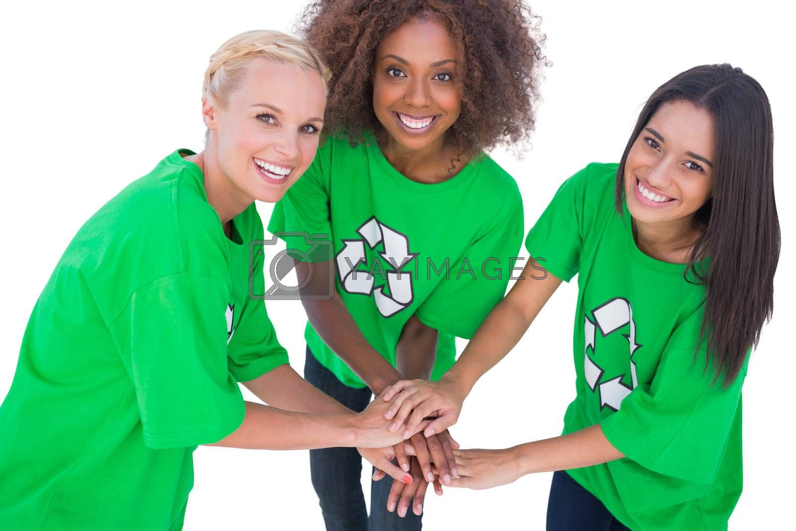 Three enviromental activists putting their hands together and smiling on white background
