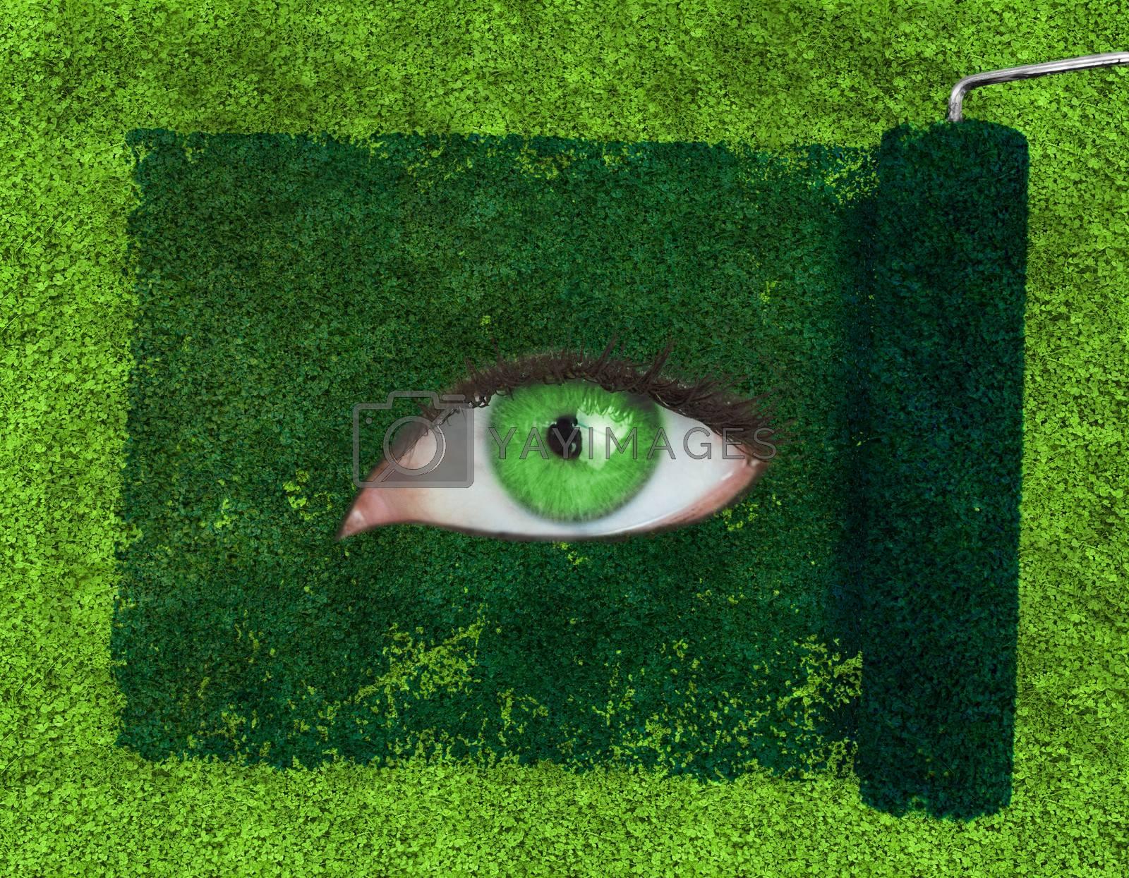Paint roller revealing a green eye over grass texture