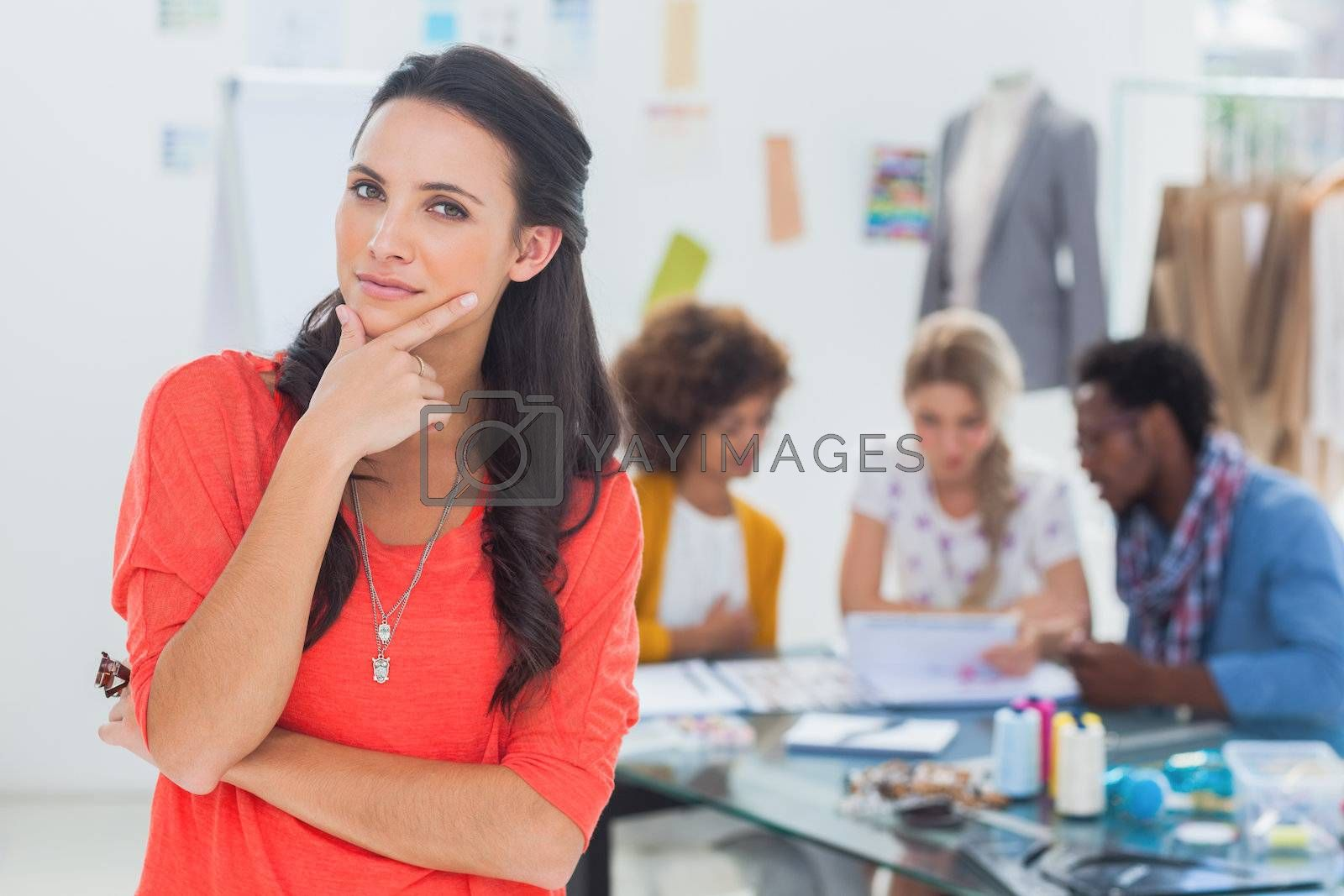 Doubtful fashion designer standing in front of her team