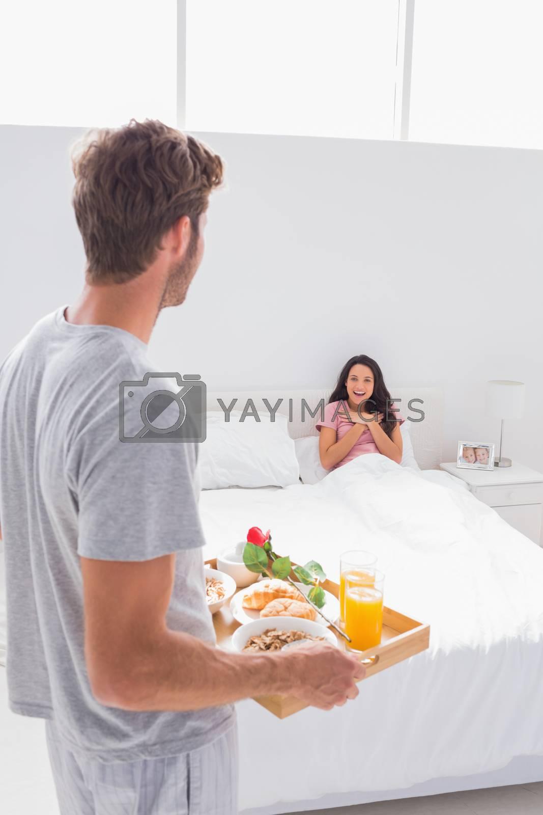 Man bringing breakfast to his surprised wife in bed