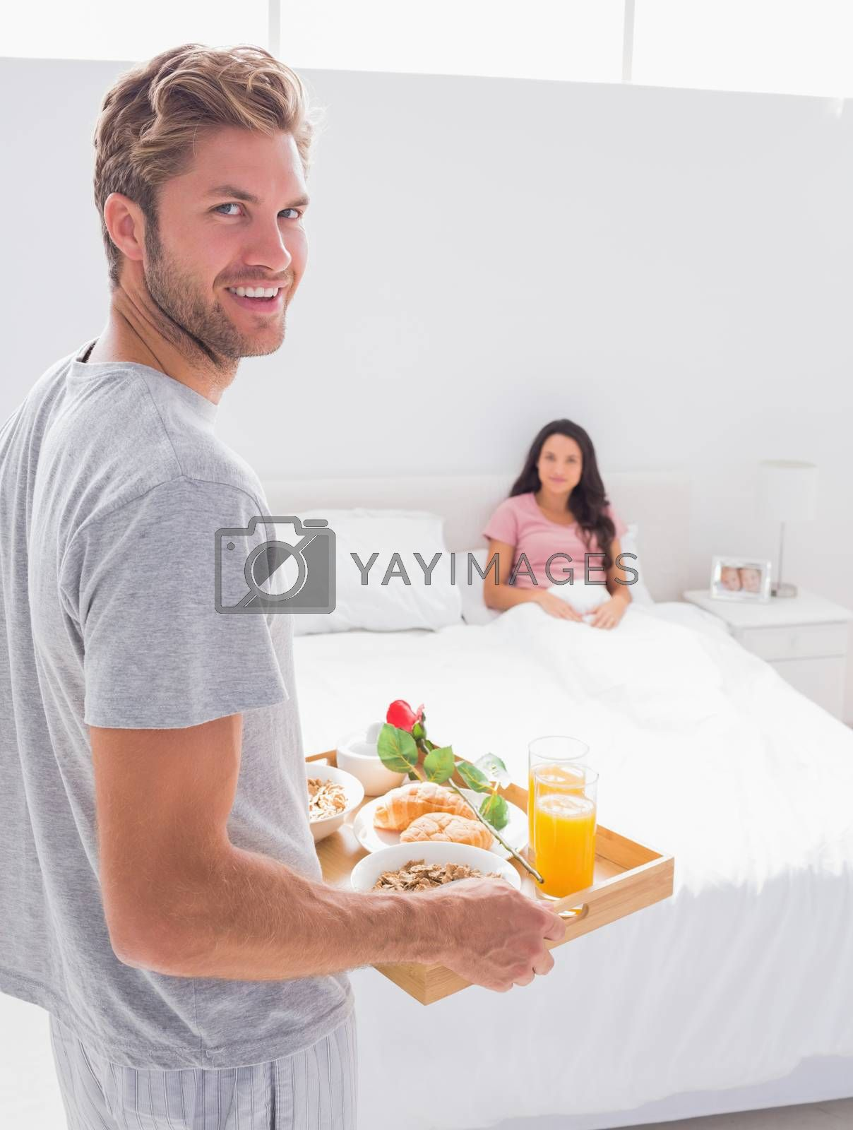 Man bringing breakfast to his wife at bed