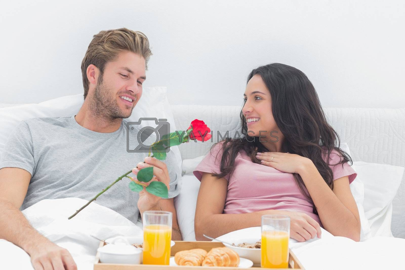 Man offering a rose to his wife during breakfast in bed
