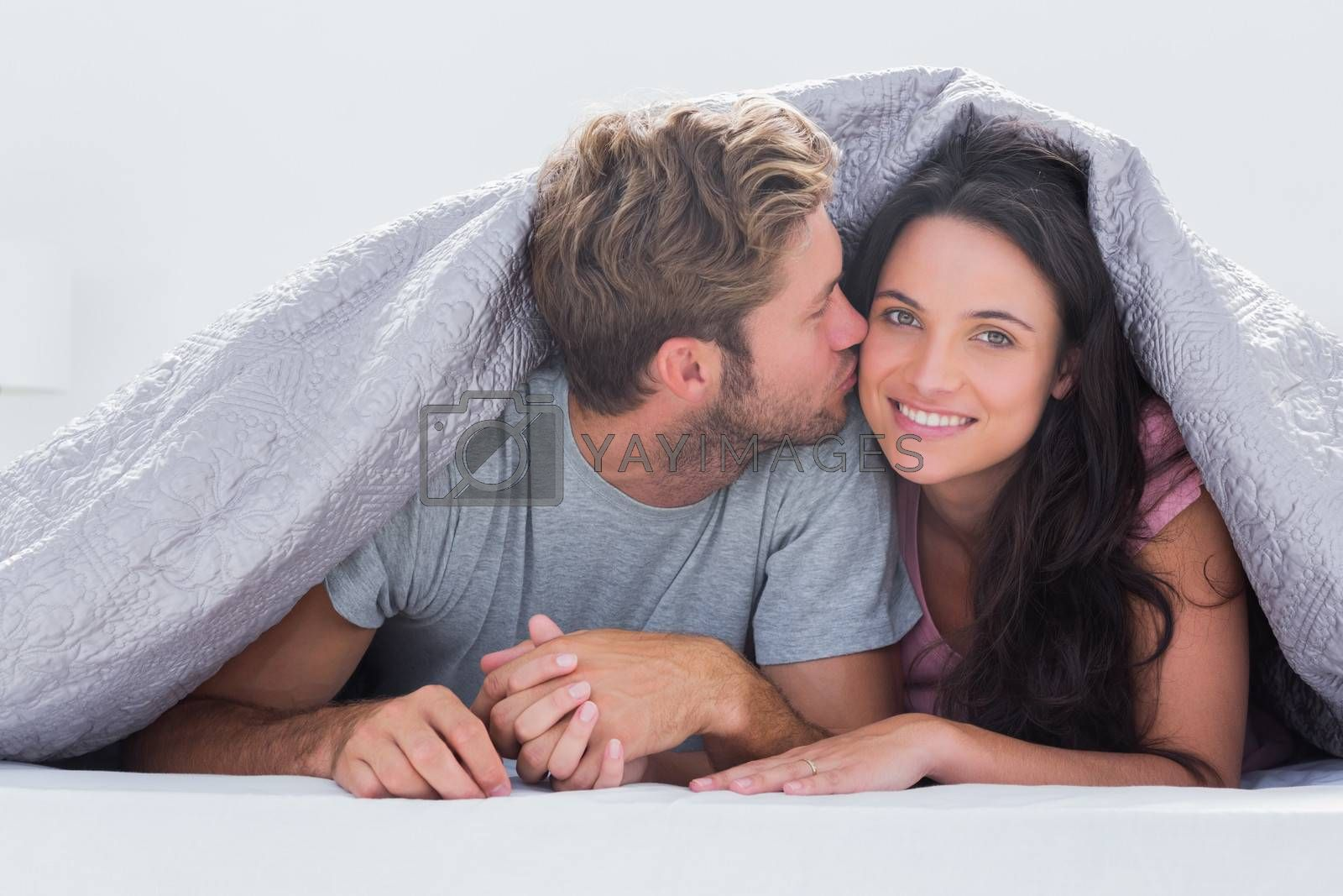 Handsome man kissing his wife under the duvet in bed