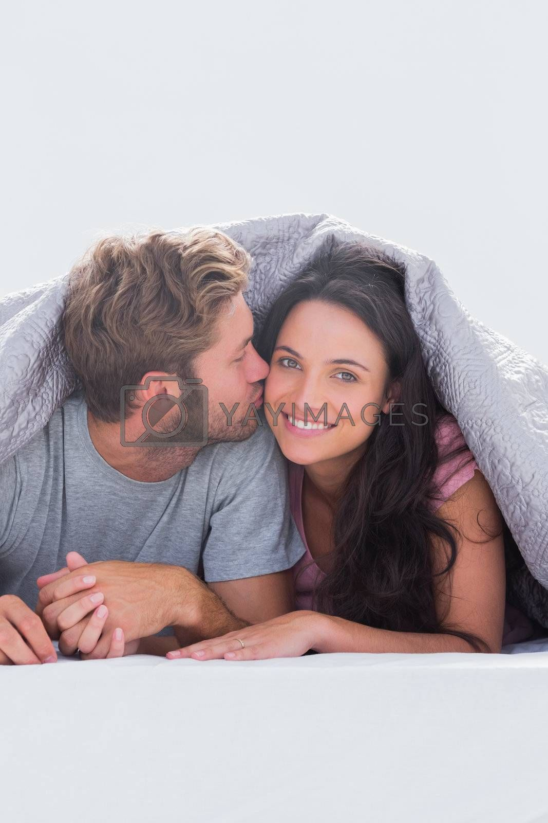 Man kissing his wife under the duvet in their bed