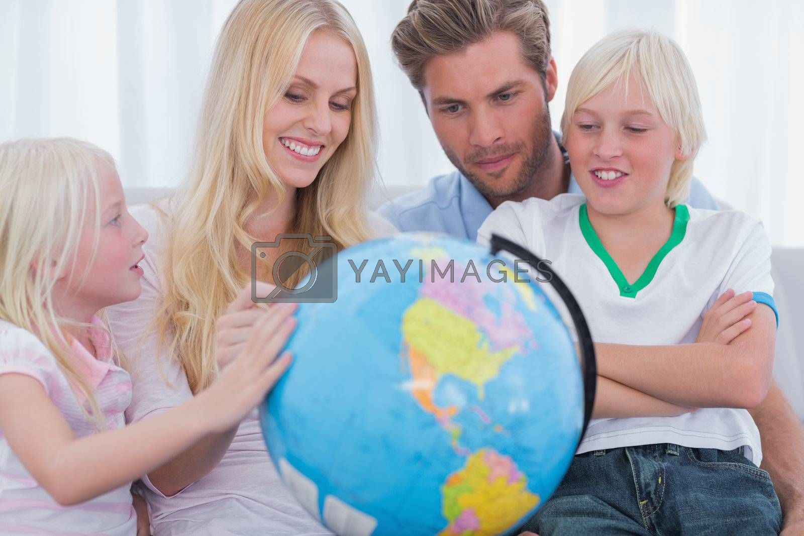 Smiling family with globe in sitting room