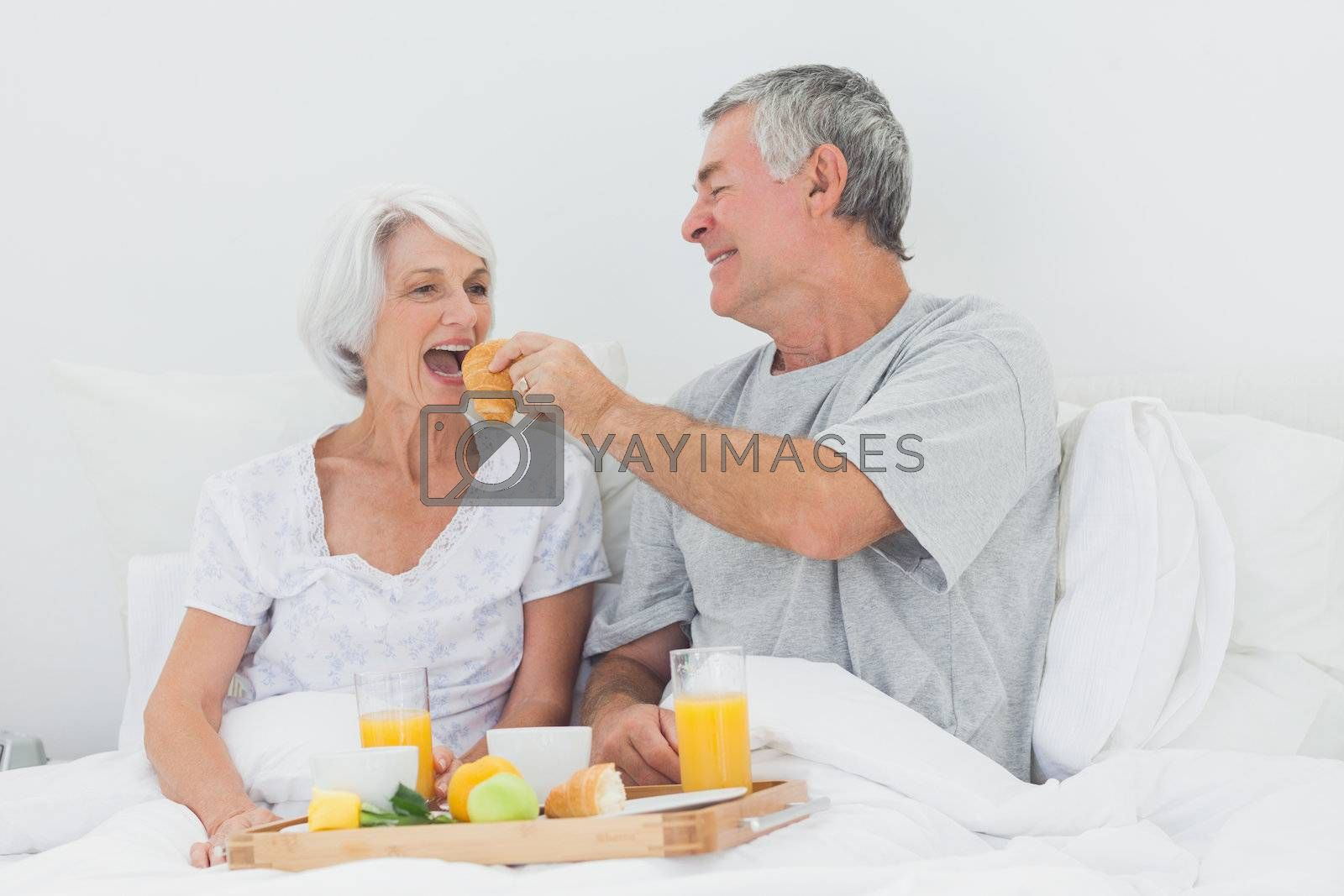 Man giving wife a croissant to wife while they are having breakfast in bed