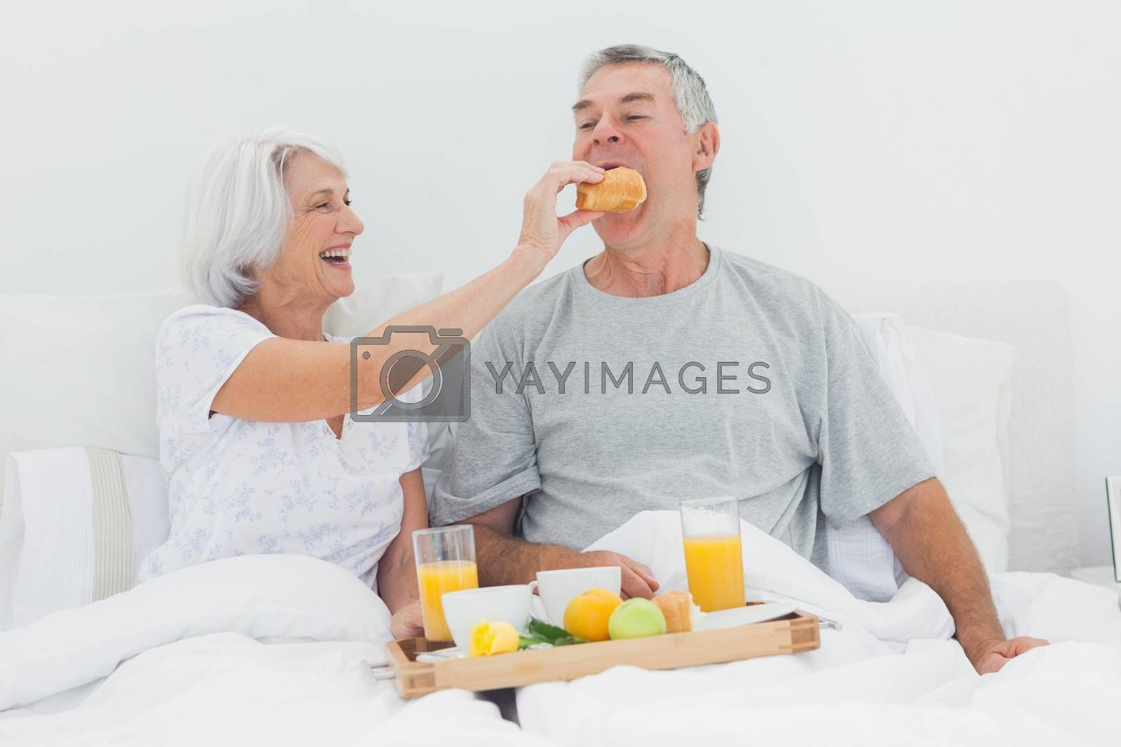 Woman giving husband a croissant while they are having breakfast in bed