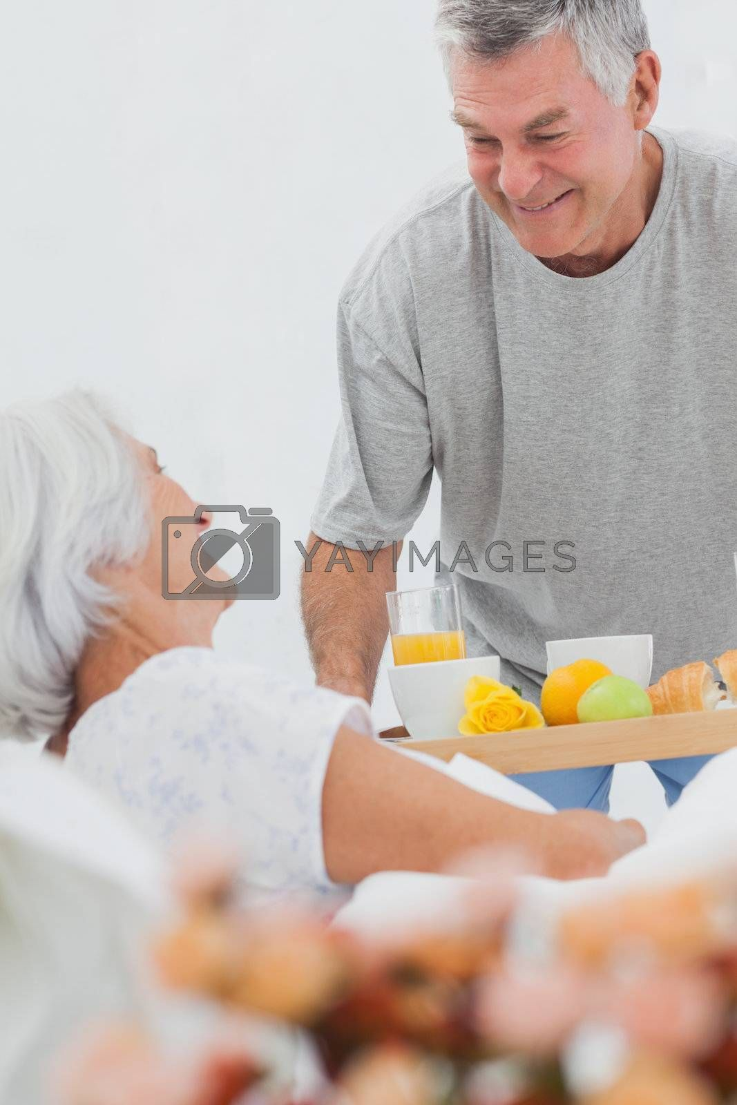 Man bringing wife breakfast in bed with orange juice and a croissant