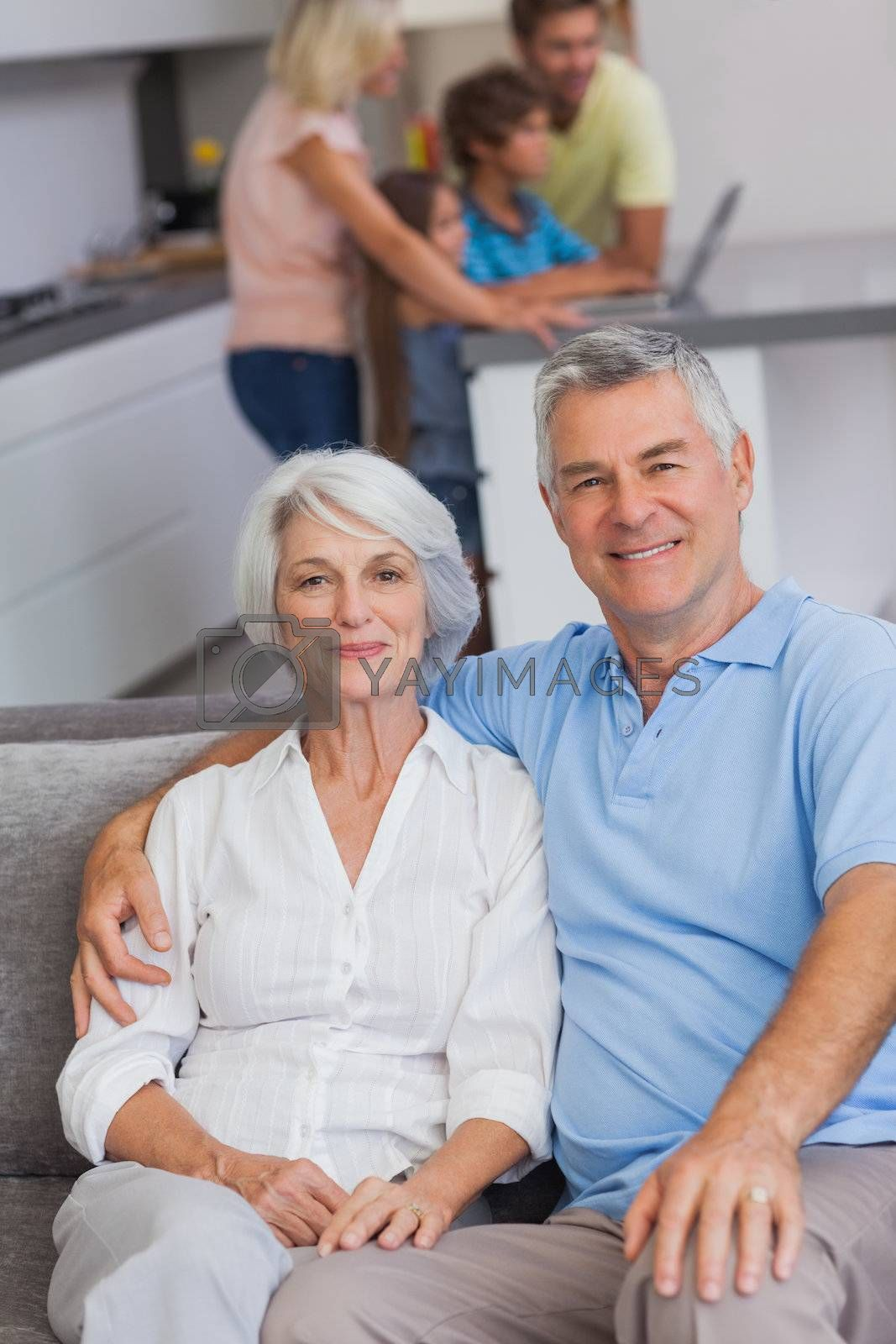 Portrait of a couple sitting on couch with their family in the kitchen behind them