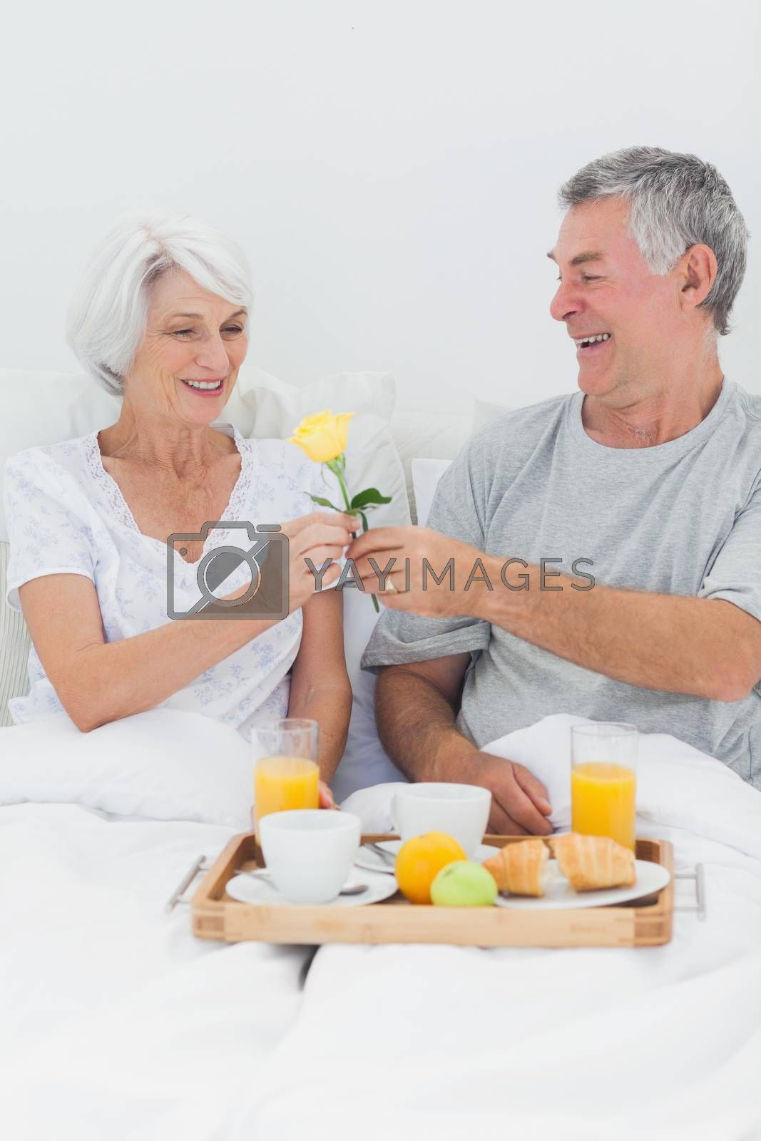 Man giving wife a yellow rose while they are having breakfast in bed