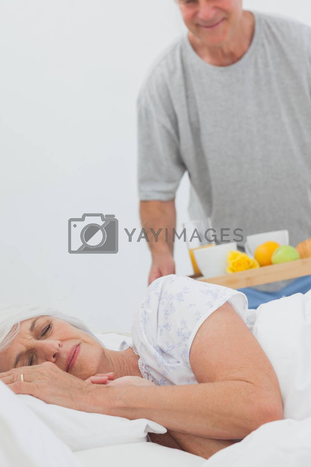 Mature man bringing sleeping wife breakfast in bed