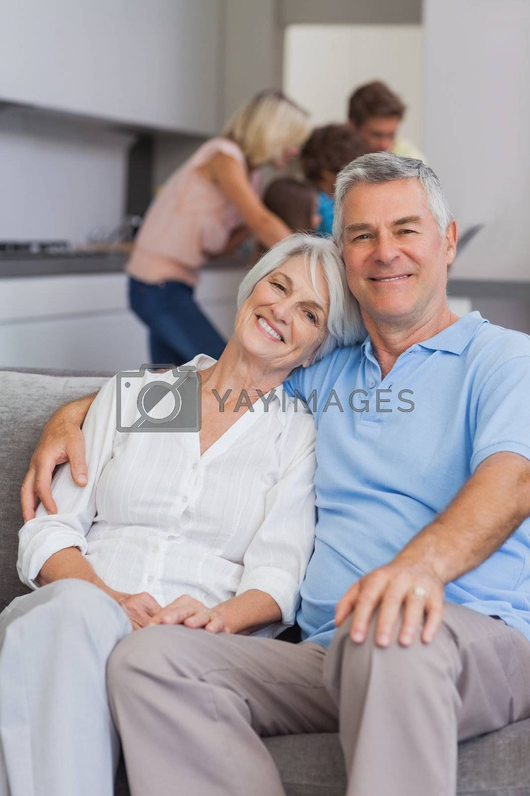 Elderly couple sitting on the couch with their family behind them