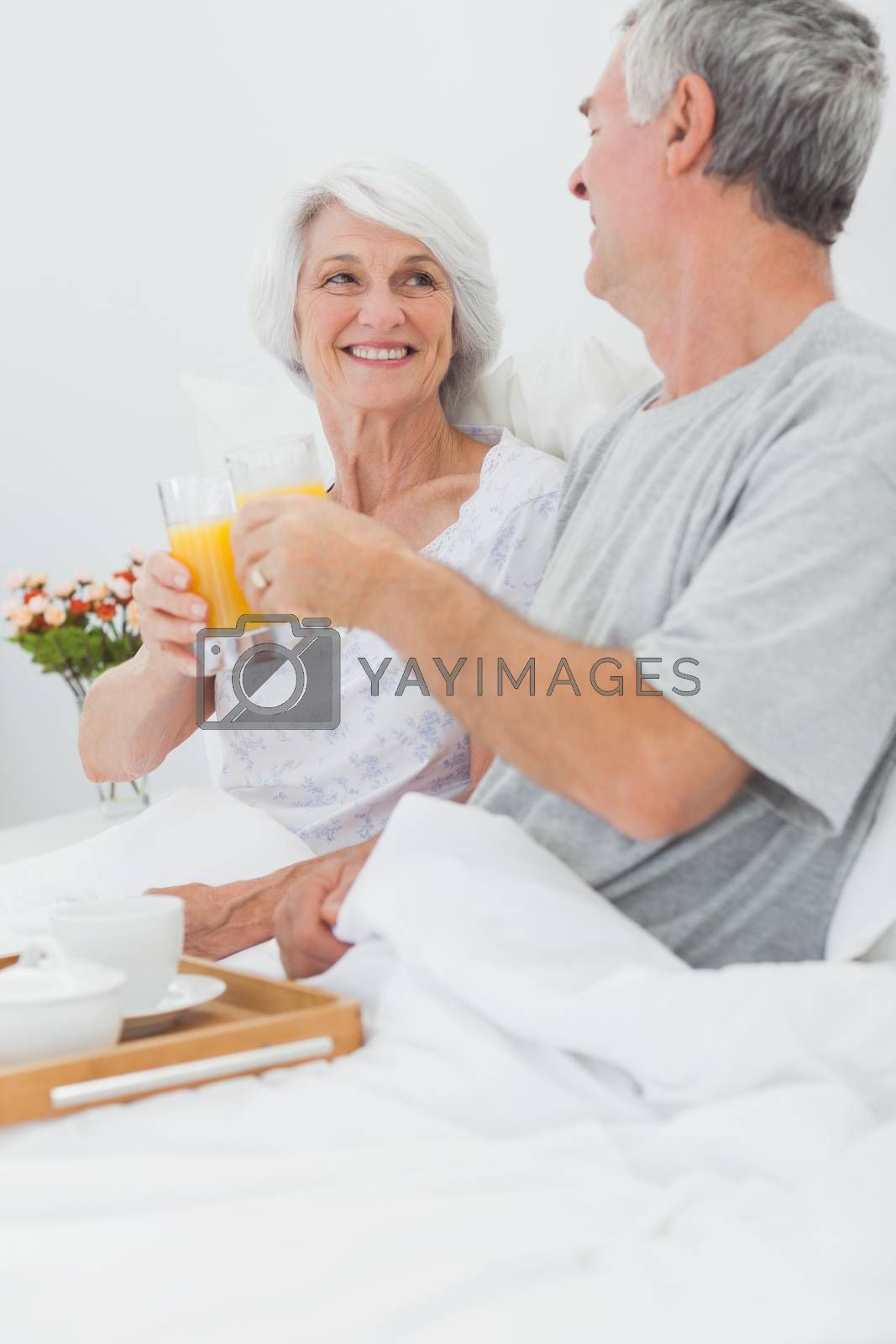 Mature couple clinking their orange juice glasses while they are having breakfast in bed