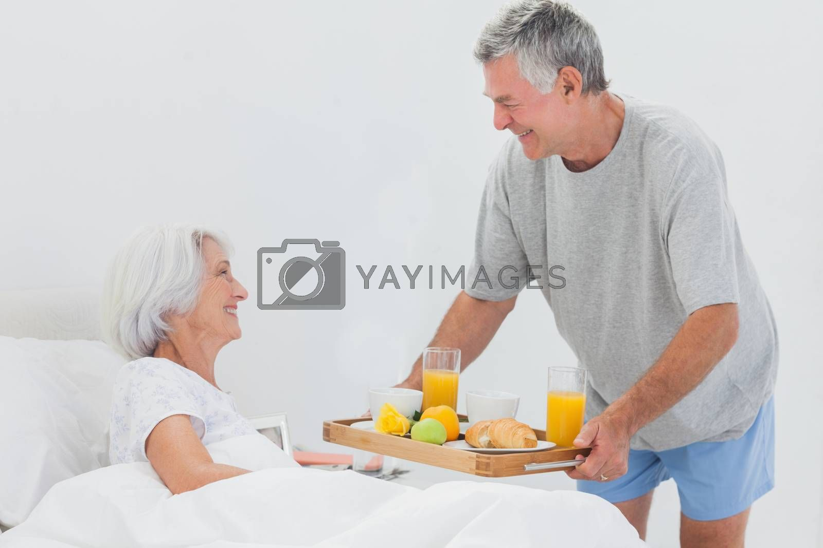 Mature man bringing wife breakfast in bed with orange juice and a croissant