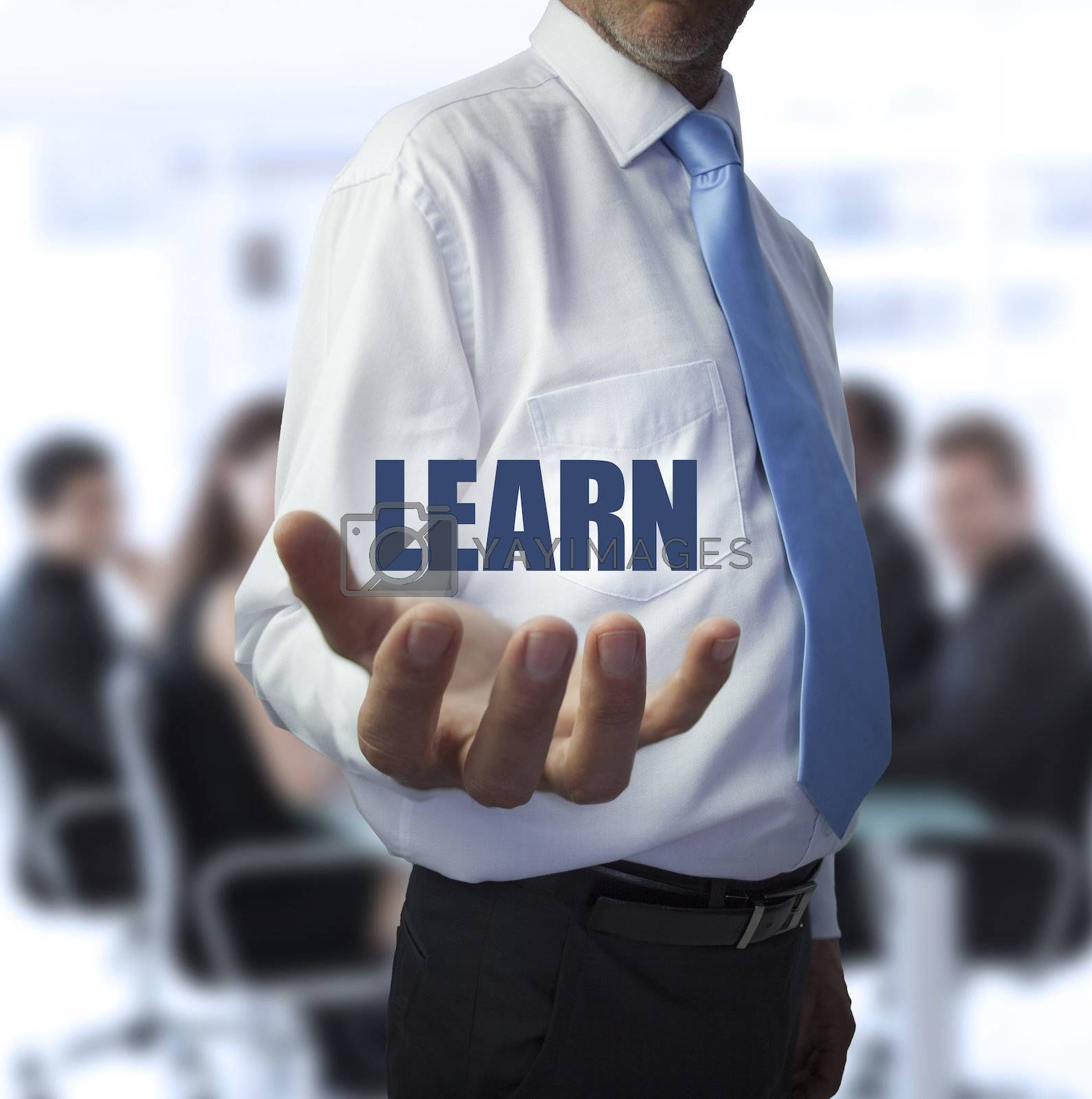 Smart businessman holding the word learn in front of a business team