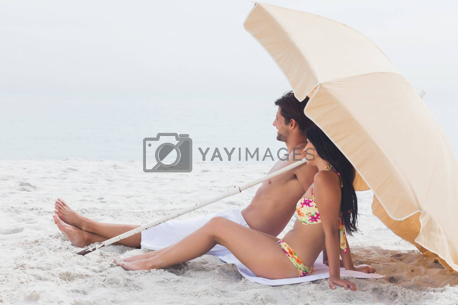Couple lying on beach towel at the beach under parasol