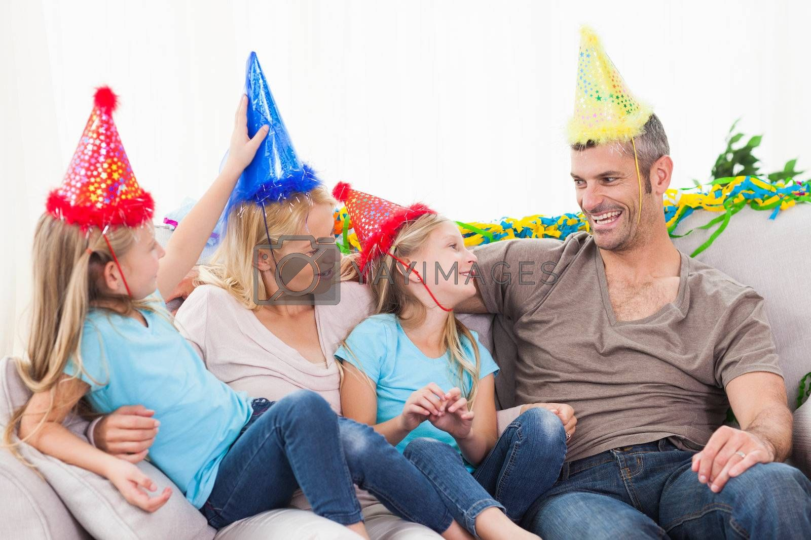 Family celebrating twins birthday sitting on a couch in the living room