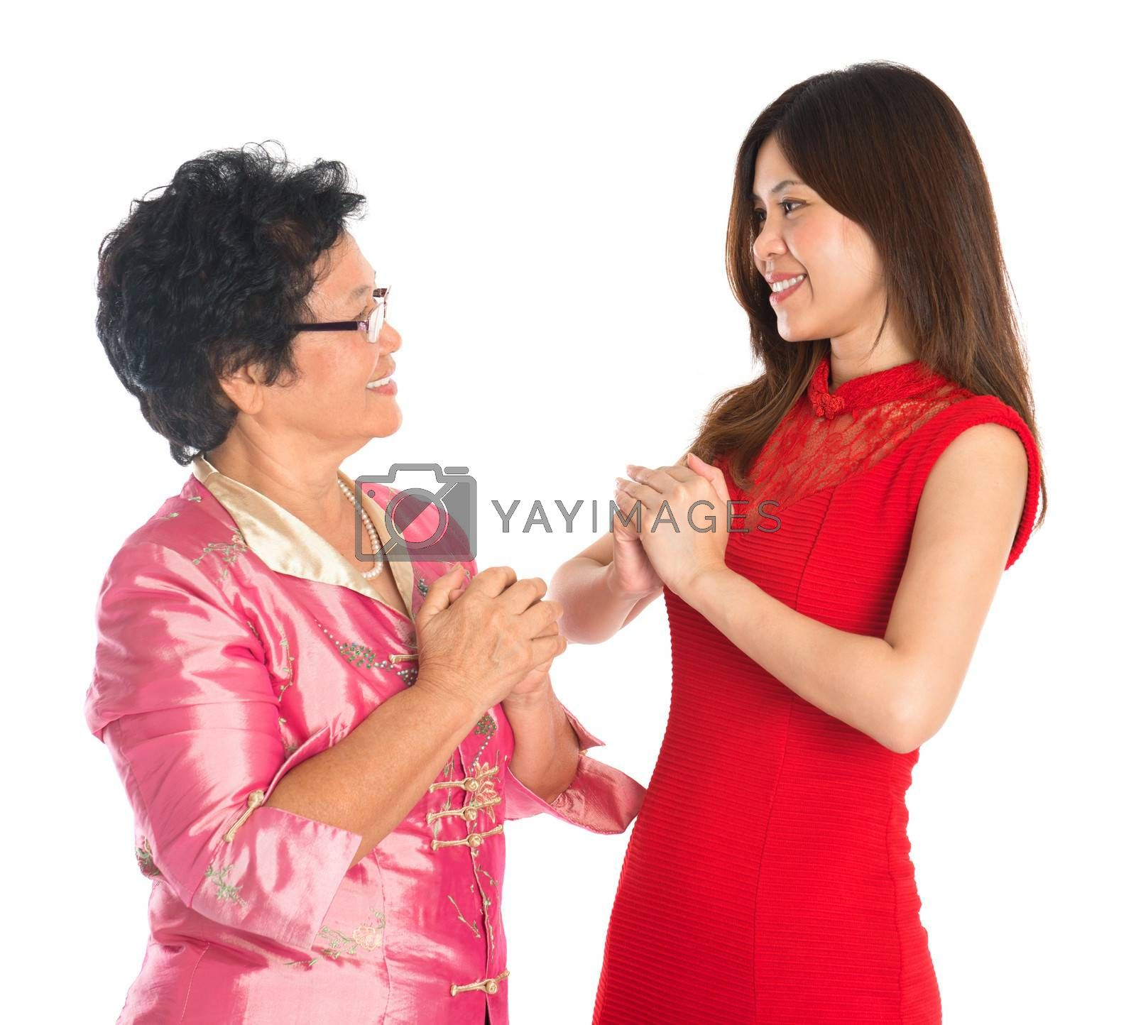Happy Chinese New Year! Chinese senior parent and daughter in traditional Chinese cheongsam greeting to each other, isolated on white background