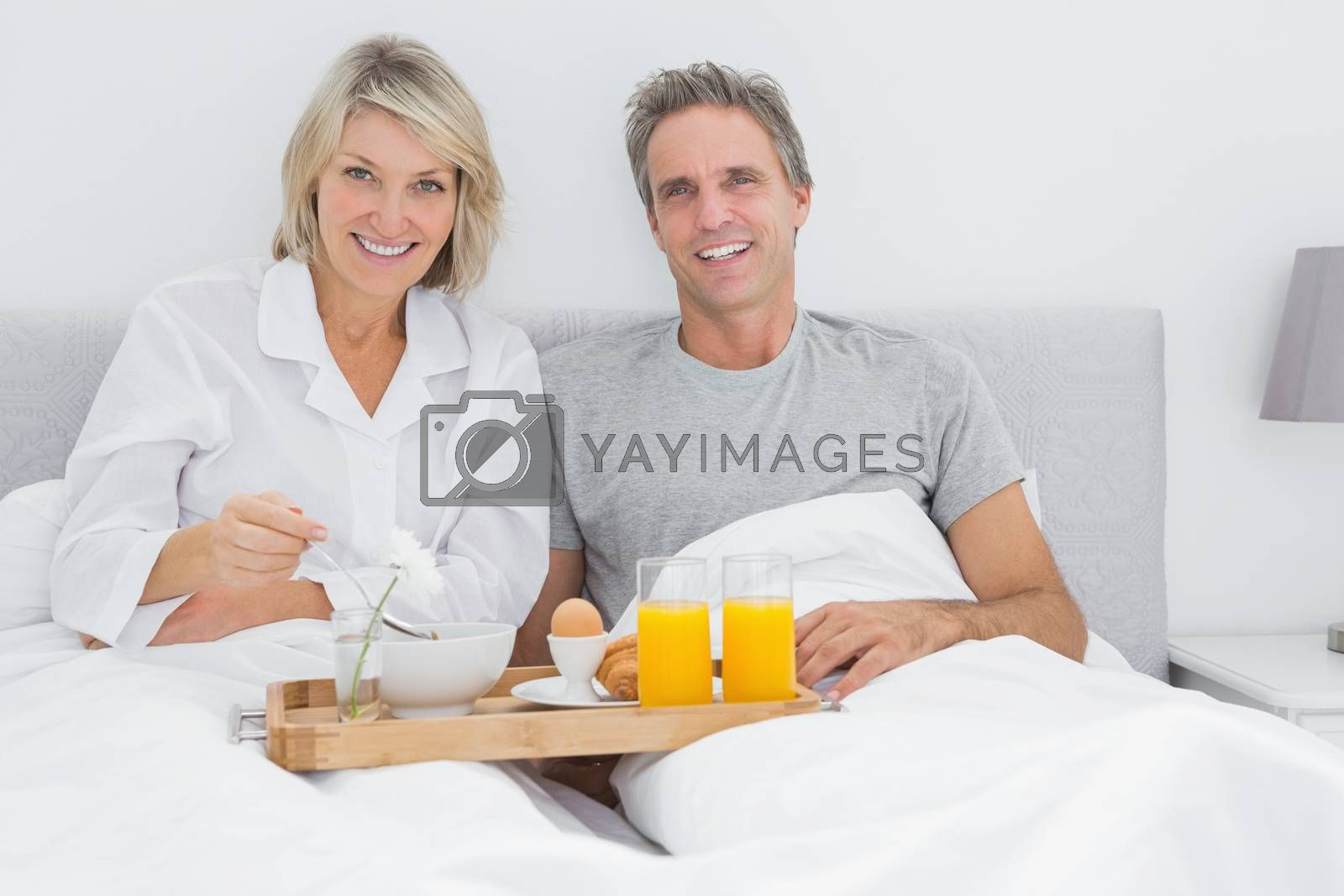 Happy couple having breakfast in bed and smiling at the camera