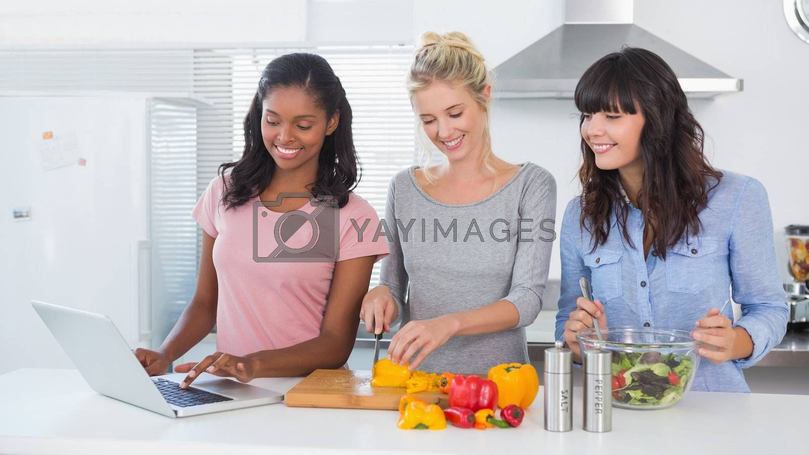 Happy friends making salad and using laptop for recipe at home in kitchen