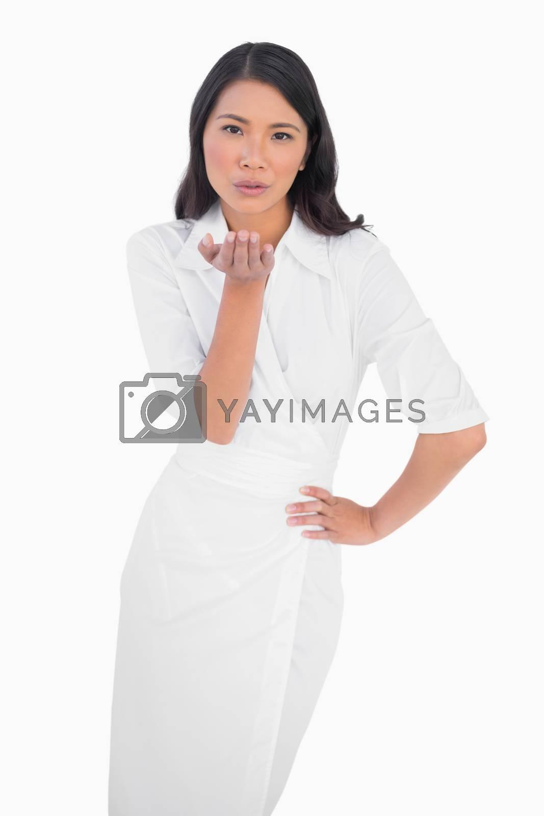 Elegant dark haired model wearing white dress kissing camera on white background