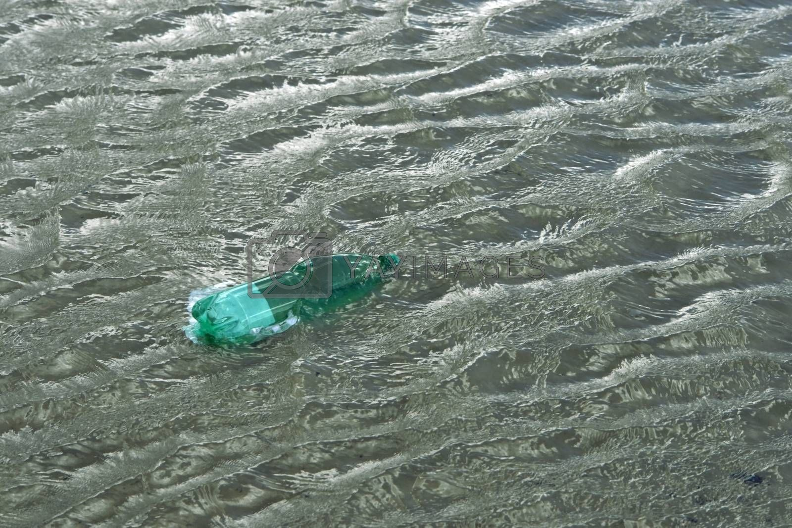 pollution theme with a green plastic bottle floating on water surface