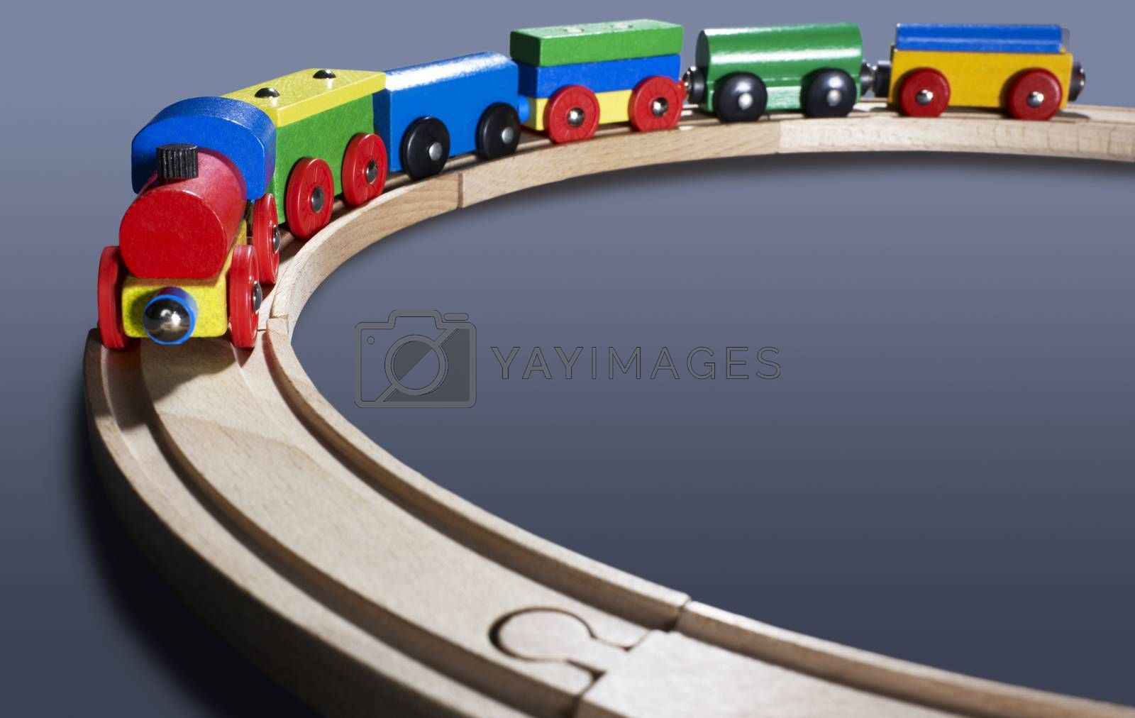 dynamic studio photography of a colorful wooden toy train dark back