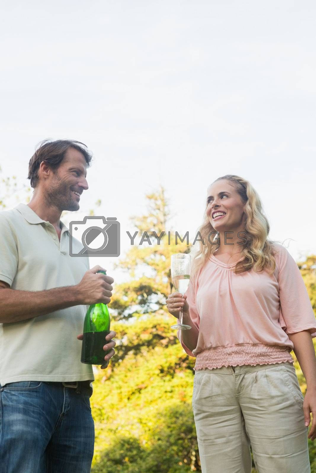 Beautiful couple having champagne together standing outside in sunshine