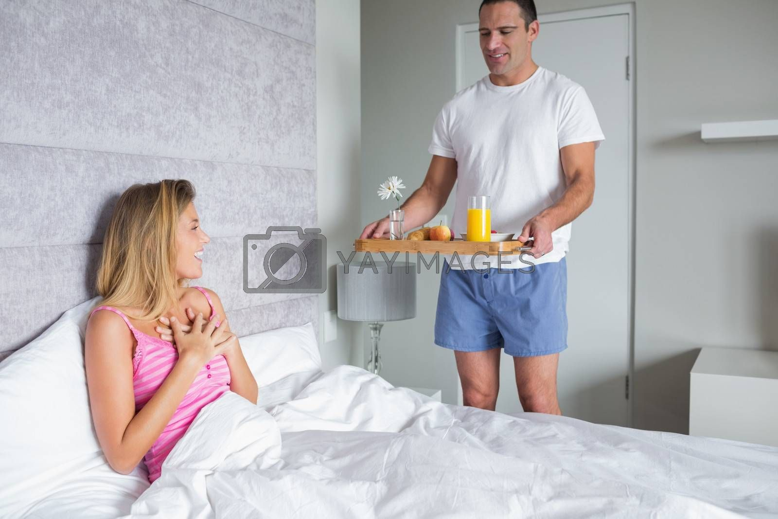 Happy woman surprised by partner bringing breakfast in bed at home in bedroom