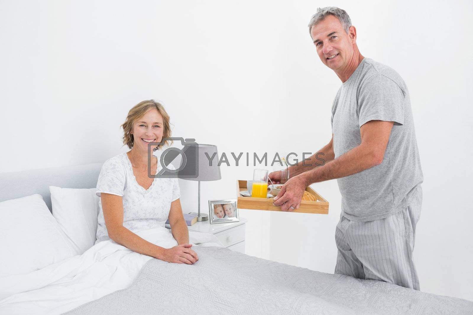 Happy husband bringing breakfast in bed to wife smiling at camera in bedroom at home