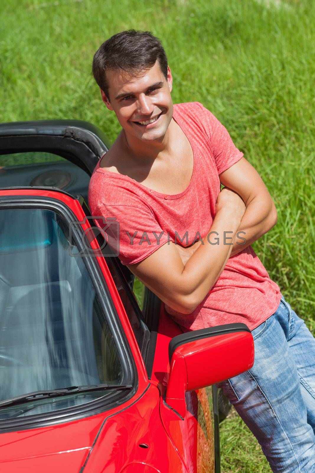 Handsome man leaning against his cabriolet by Wavebreakmedia
