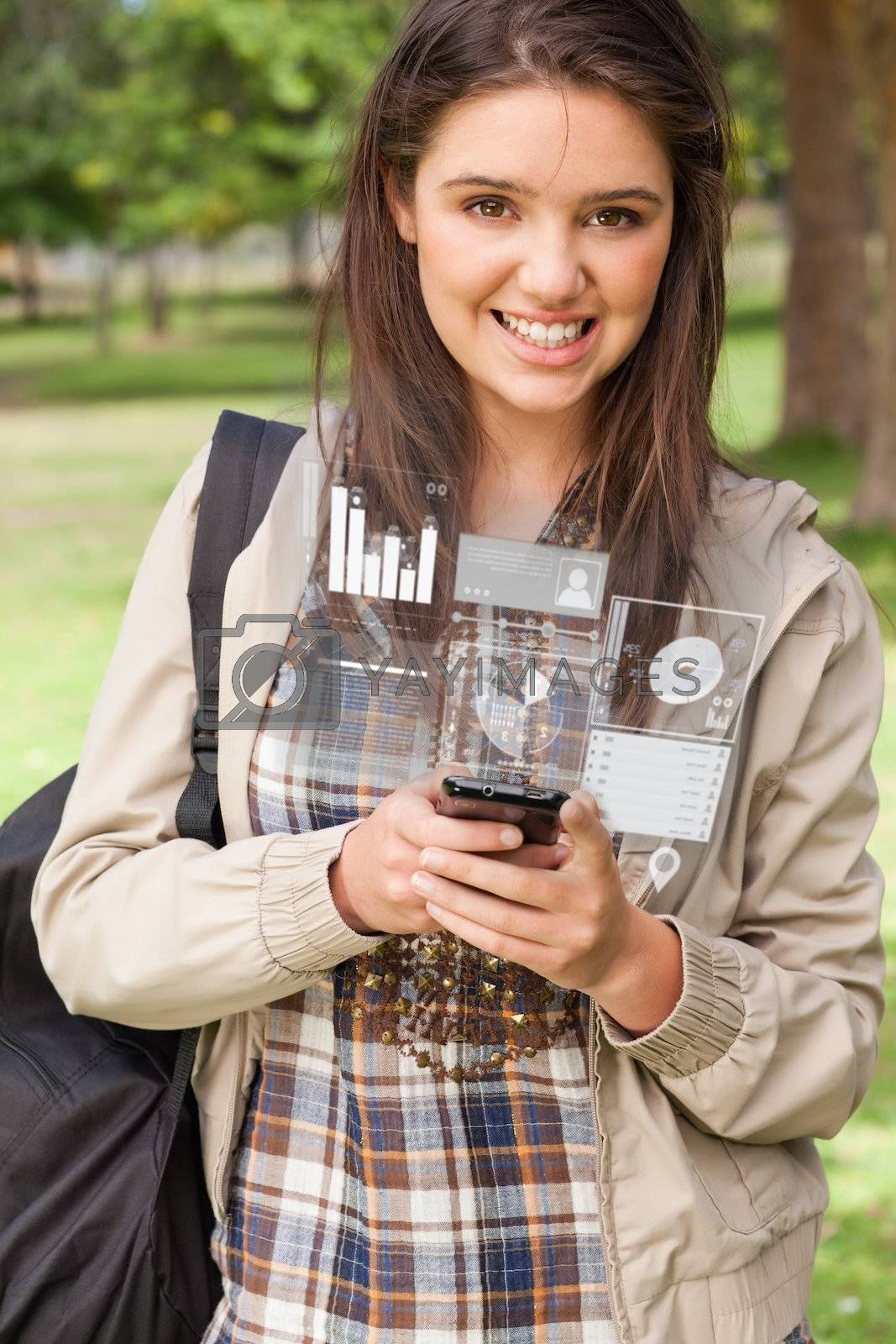 Happy young woman working on her futuristic smartphone by Wavebreakmedia