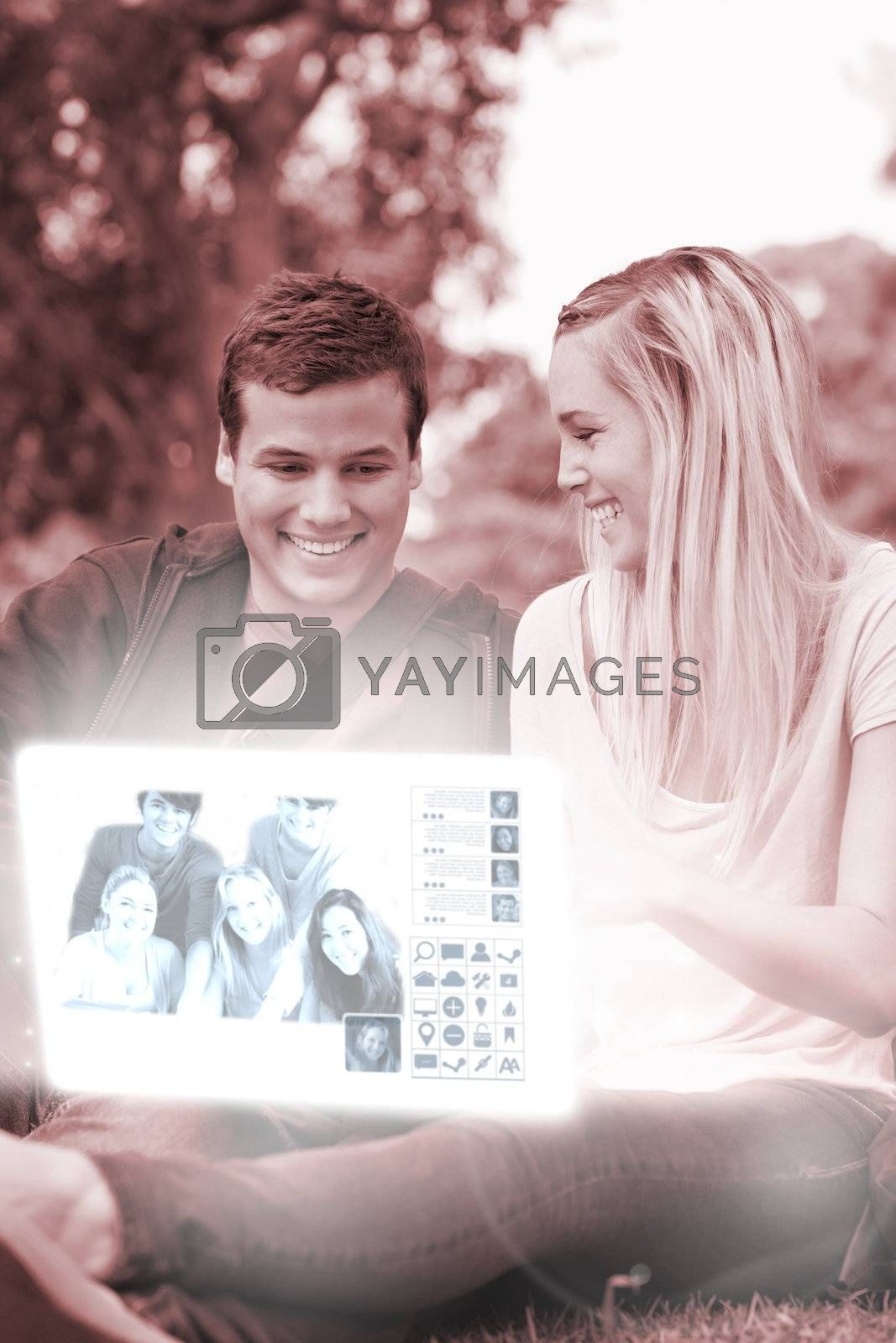 Cheerful young couple watching photos on digital interface by Wavebreakmedia