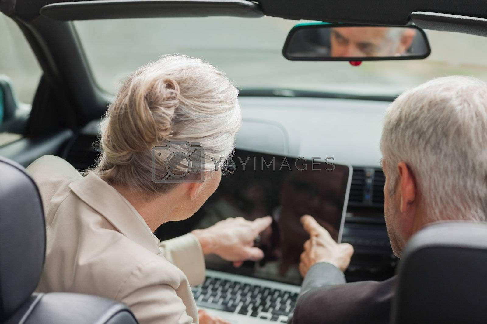 Business people working together on laptop in classy cabriolet by Wavebreakmedia