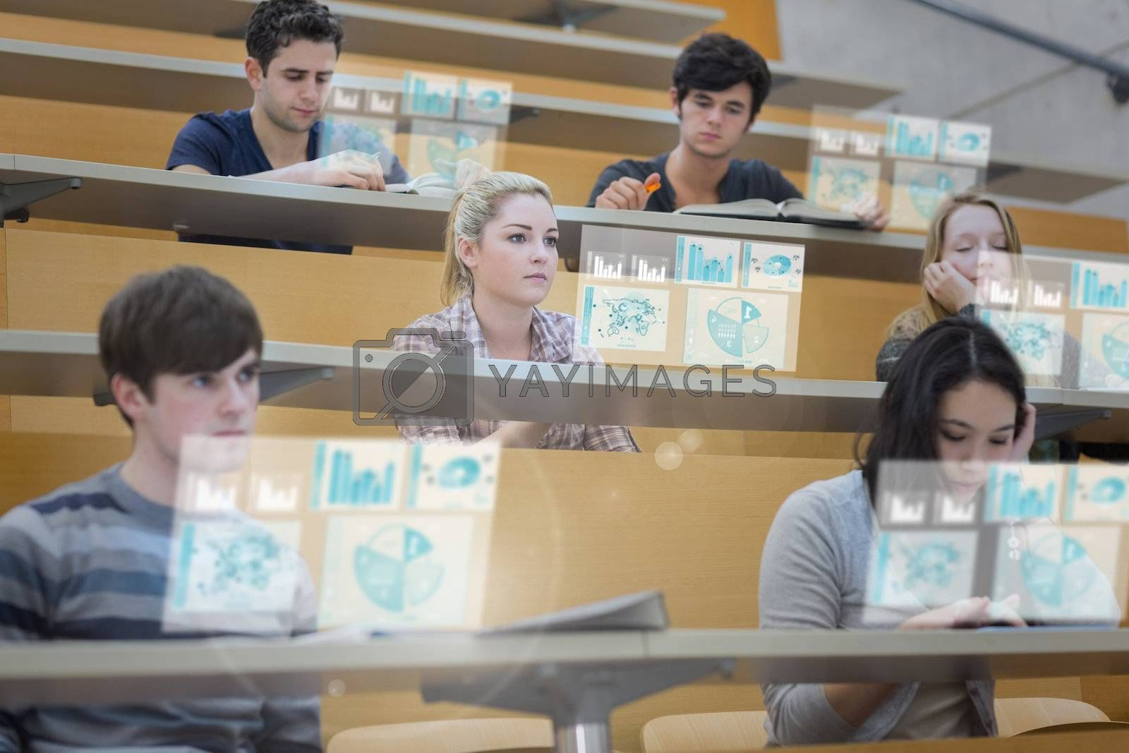 Focused students in lecture hall working on their futuristic tablet by Wavebreakmedia