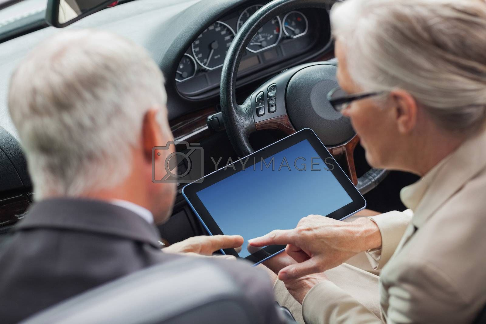Mature partners working together on tablet in classy convertible by Wavebreakmedia