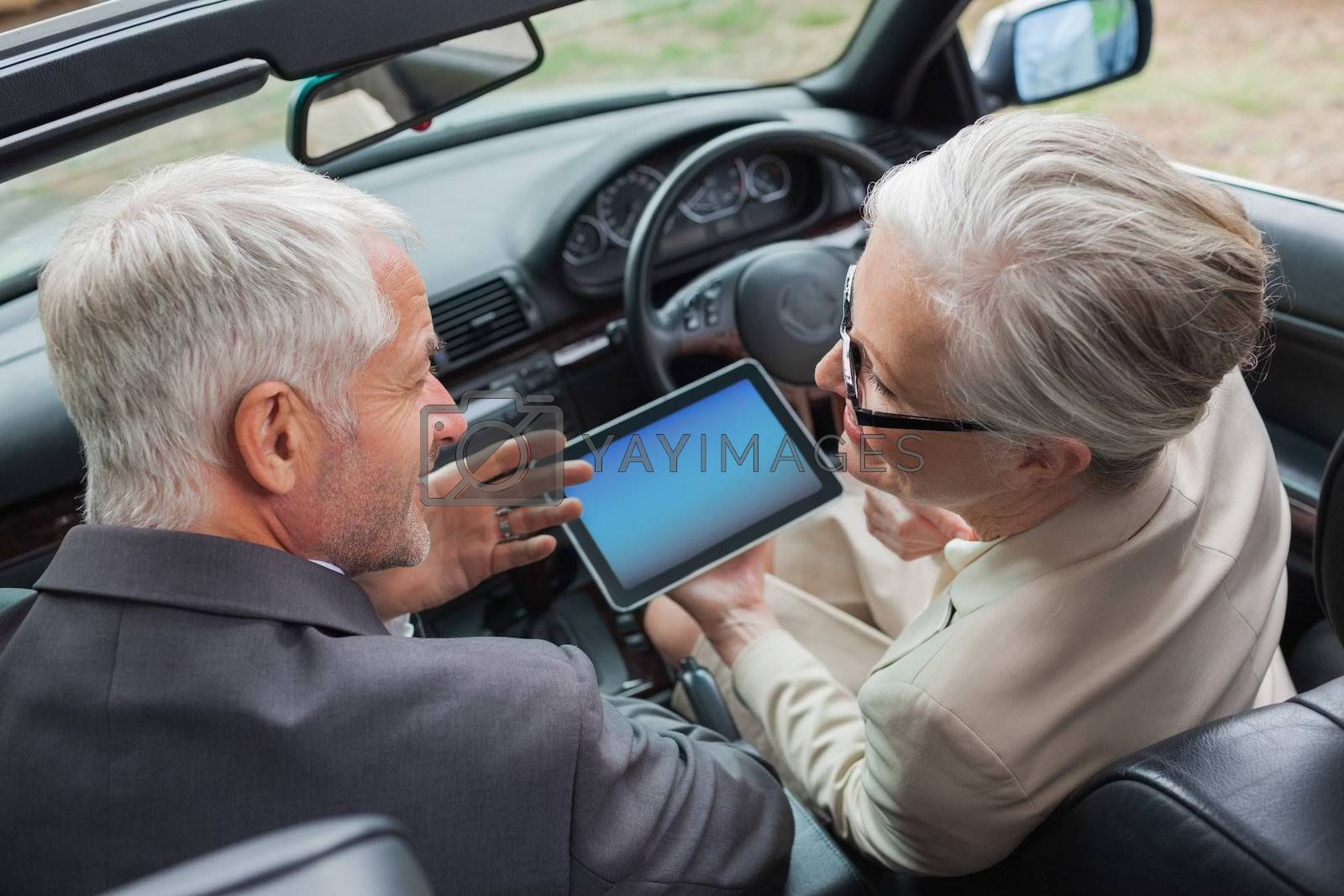 Smiling mature partners working together on tablet in classy car by Wavebreakmedia