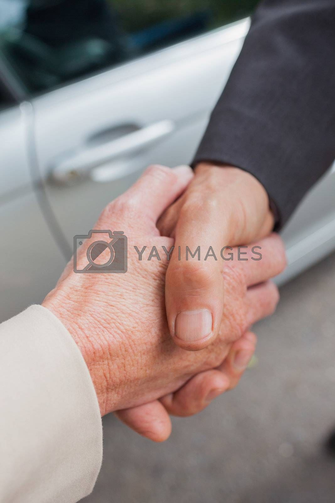 Close up on business people shaking hands by Wavebreakmedia
