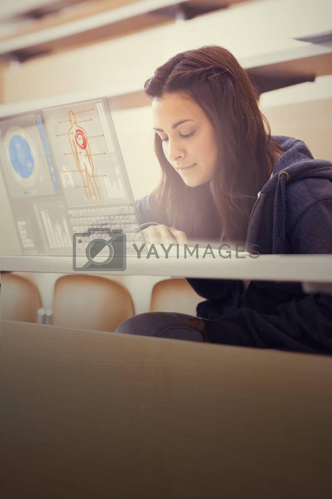 Focused college student working on her digital laptop by Wavebreakmedia