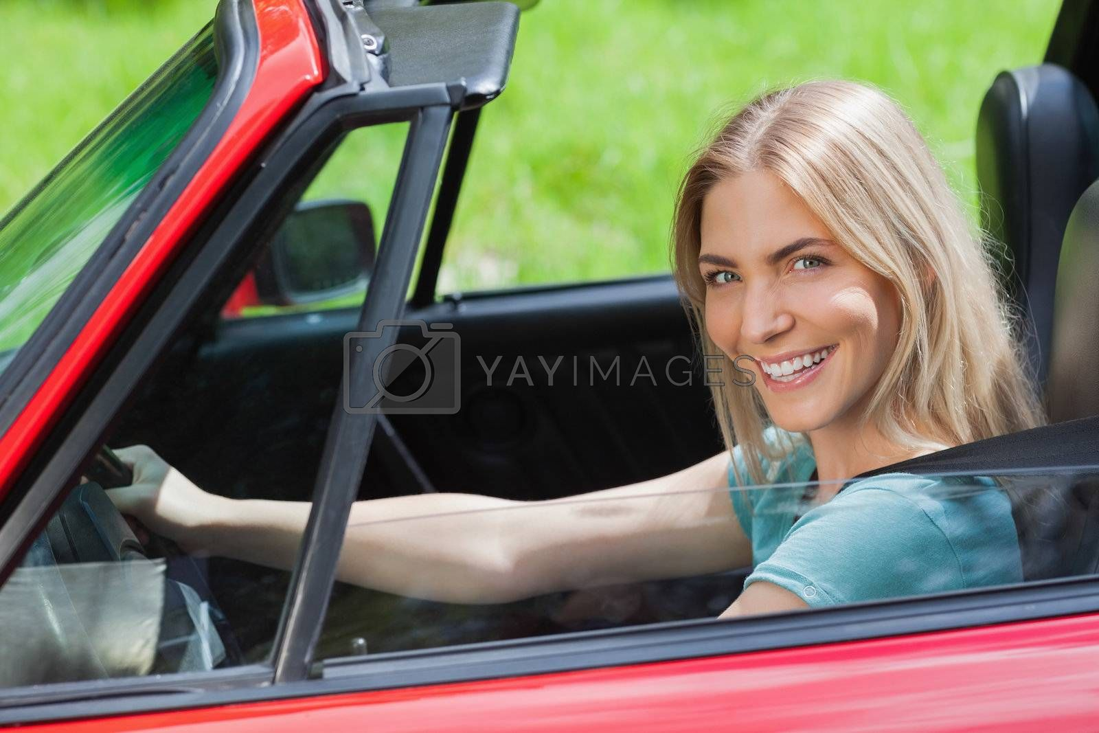 Cheerful woman driving red cabriolet by Wavebreakmedia
