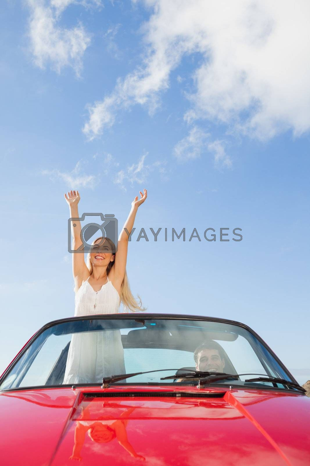 Cheerful woman standing in cabriolet while her boyfriend driving by Wavebreakmedia