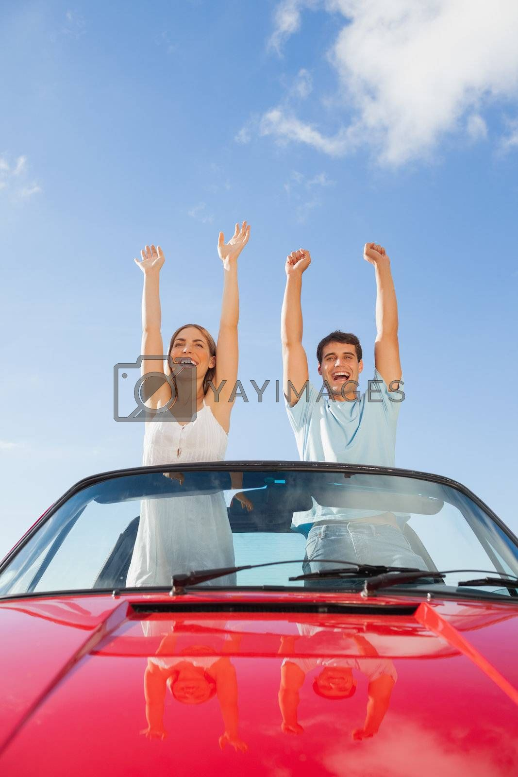 Cheerful couple standing in red cabriolet by Wavebreakmedia