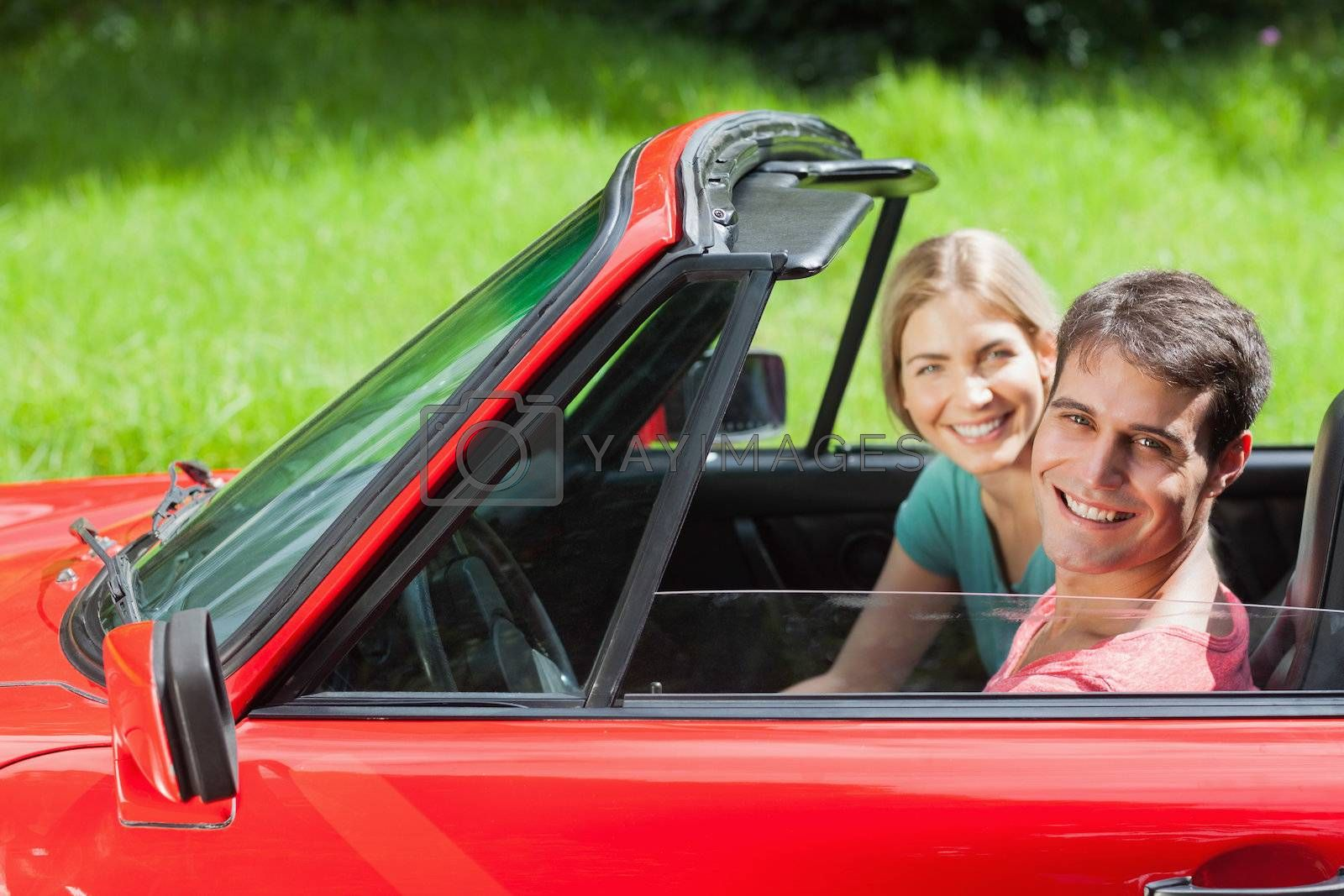 Cheerful young couple having a ride in red cabriolet by Wavebreakmedia
