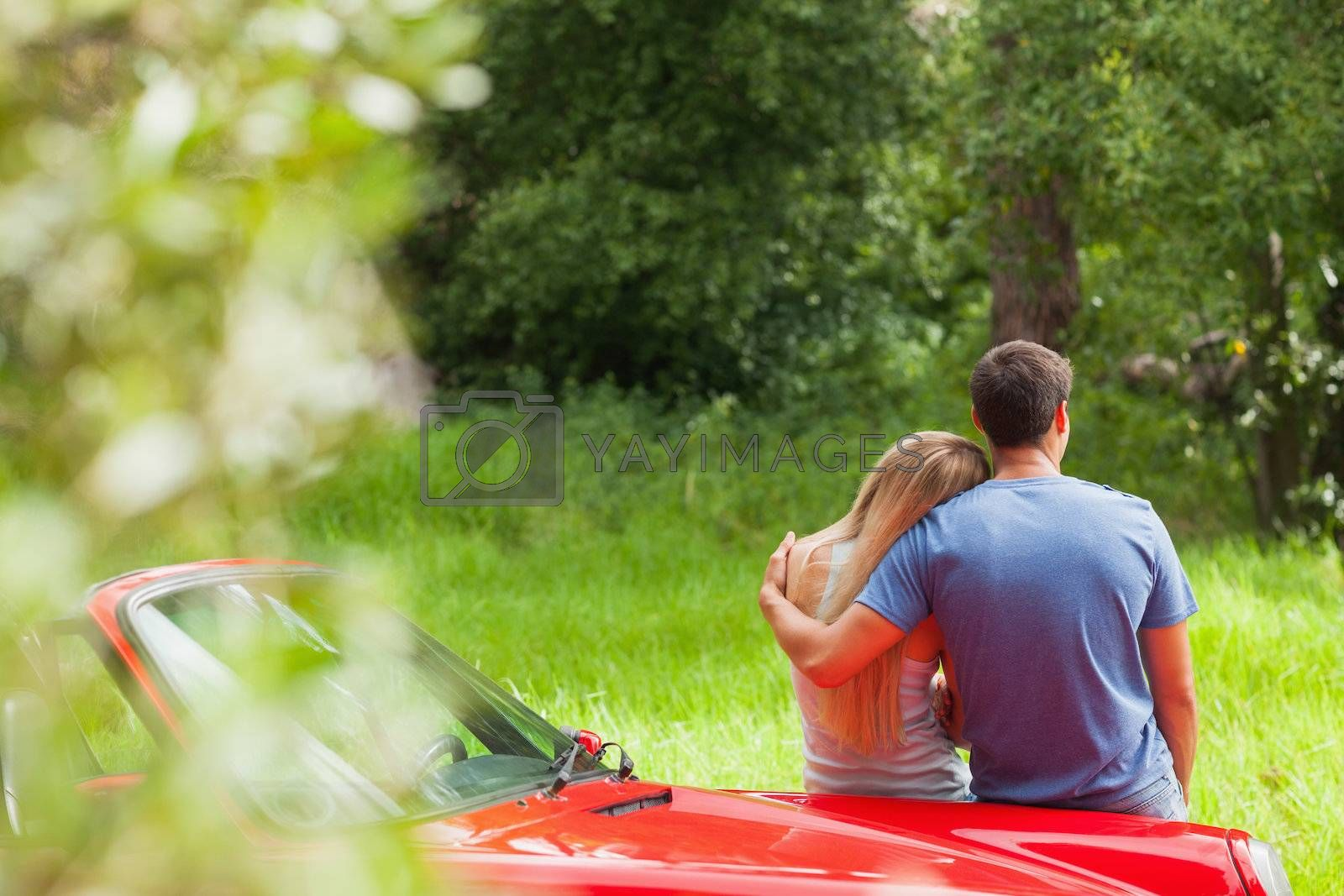 Loving couple admiring nature while leaning on their cabriolet by Wavebreakmedia