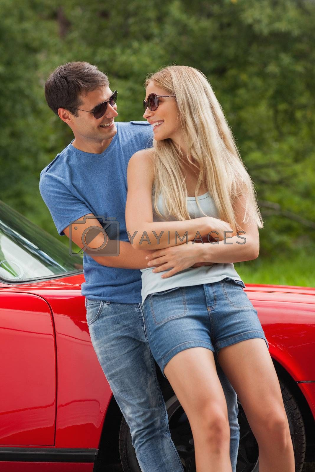 Smiling couple hugging and leaning against cabriolet by Wavebreakmedia