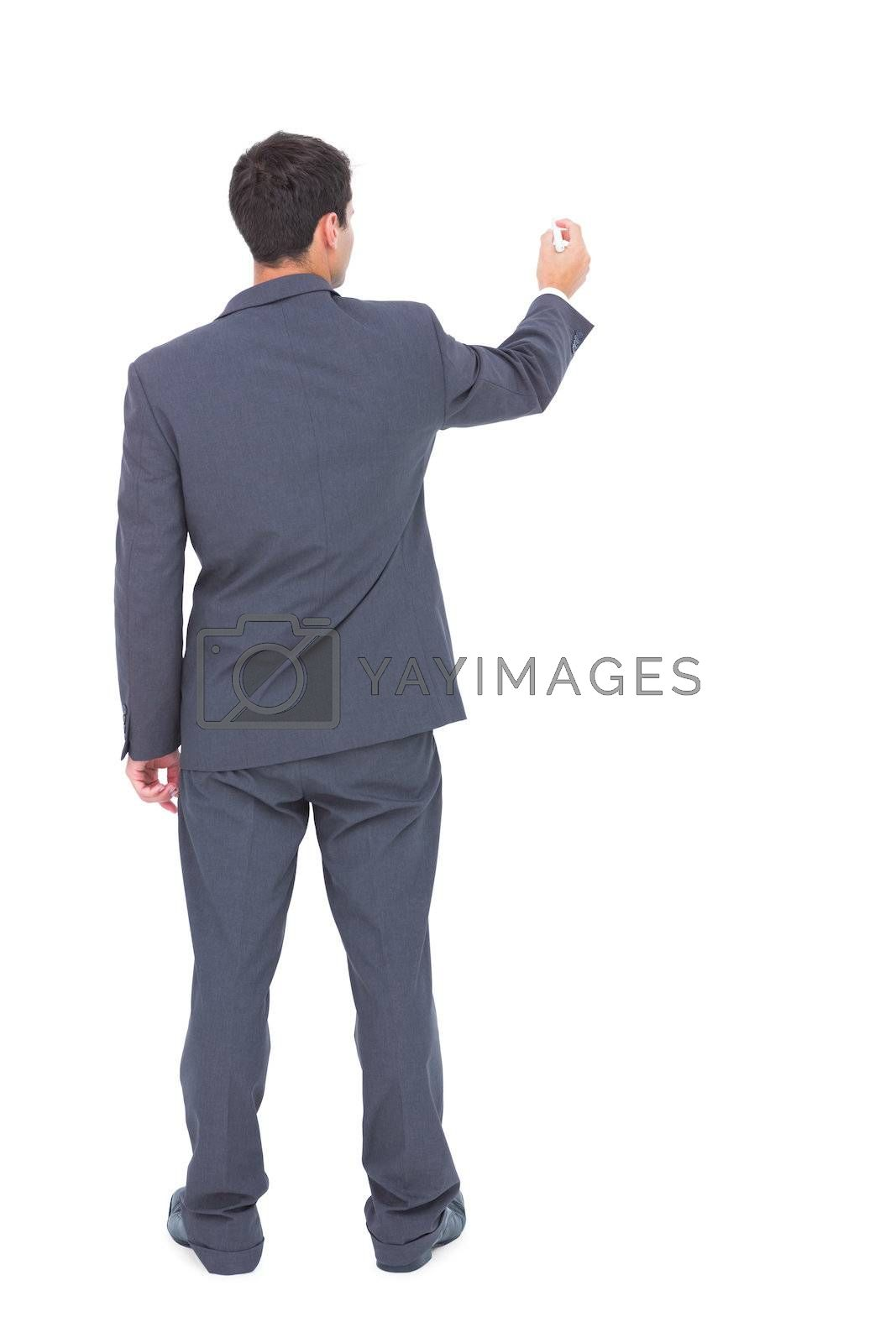 Businessman standing back to camera writing with marker by Wavebreakmedia