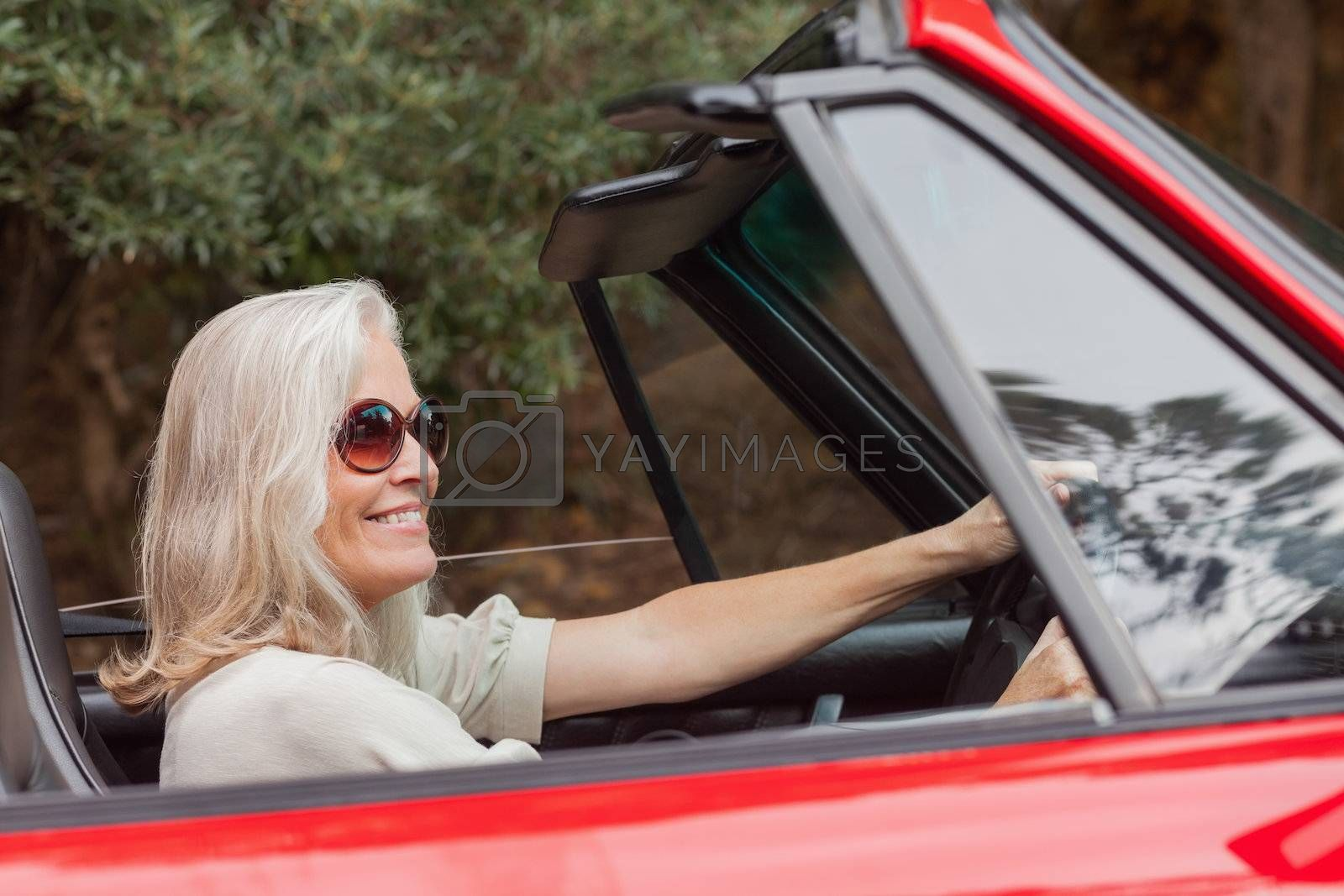 Happy mature woman with sunglasses driving red convertible by Wavebreakmedia