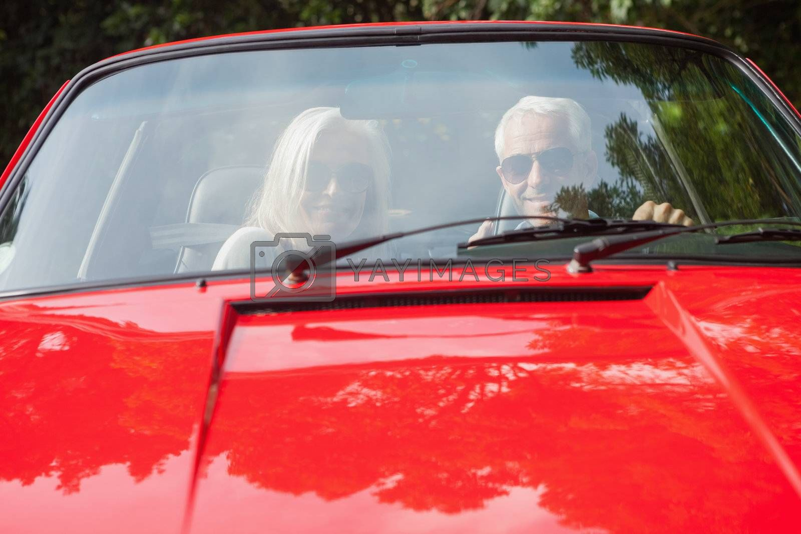 Smiling mature couple in red cabriolet by Wavebreakmedia