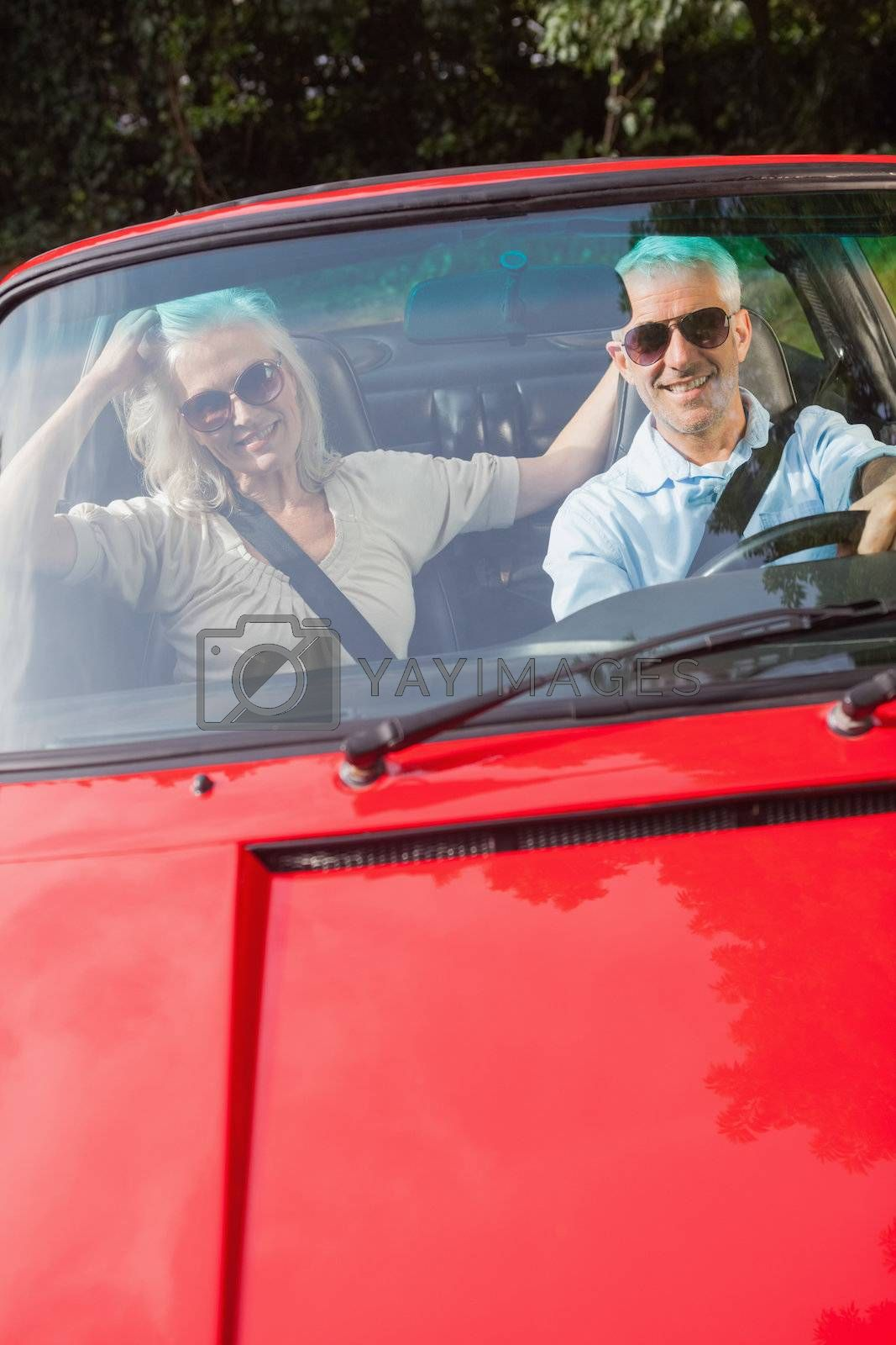 Mature couple in red cabriolet smiling at camera by Wavebreakmedia