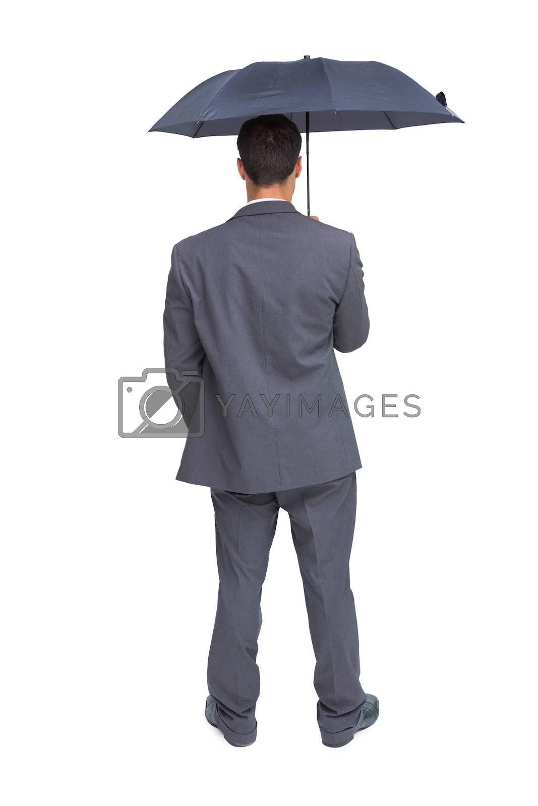 Rear view of classy businessman holding grey umbrella by Wavebreakmedia